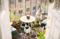 Biely stolík s kovovými nohami na malom balkóne