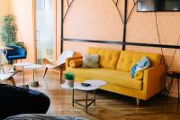 Žltá pohovka v retro obývačke s tehlovou stenou