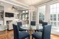 Sivé čalúnené jedálenské stoličky a okrúhly stôl so sklenenou doskou