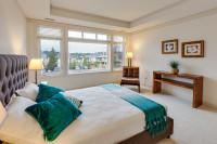 Čalúnená manželská posteľ a kožené kreslo vo veľkej spálni