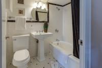 Elegantné biele umývadlo a čiernobiele doplnky v klasickej kúpeľni