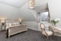 Manželská posteľ a baroková stolička v podkrovnej spálni