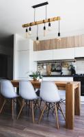 Biele plastové stoličky a masívny drevený stôl v priestrannej kuchyni