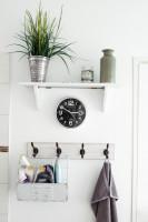 Nástenné hodiny a háčiky v bielej škandinávskej kúpeľni