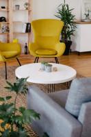 Žlté dizajnové kreslá a biely stolík v retro obývačke