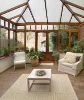 Svetlé kreslo, stolička, jednoduchý stolík a koberec v zimnej záhrade