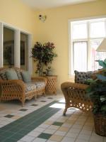 Prútená lavica a kreslo so sadou vankúšov, prútený stolík so sklom a rastliny