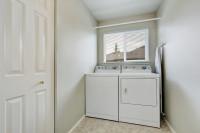Menšia práčovňa na práčku, sušičku a žehliacu dosku s oknom