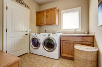 Práčovňa s umývadlom, hnedou zavesenou skrinkou a košom na prádlo