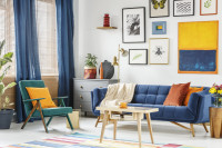 Tyrkysové retro kreslo a modrá pohovka vo veselej obývačke