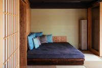 Veľká manželská posteľ pri drevenej stene