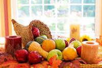 Jablká, ozdobné tekvičky a sviečky na farebných listoch