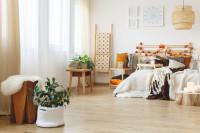 Manželská posteľ s dreveným záhlavím, vankúšmi a dekami