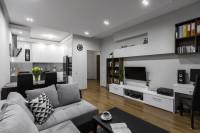 Sivá pohovka, čierny stolík a biele skrinky pod TV
