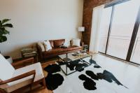 Hnedý kožený gauč, biele kreslo a kožušina na podlahe