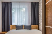 Malá spálňa s farebne zladenými závesmi a vankúšmi