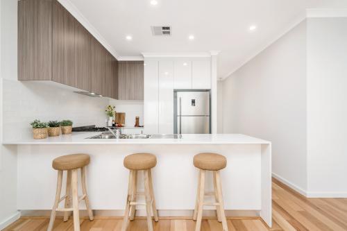Bielo-hnedá kuchyňa s barovým sedením