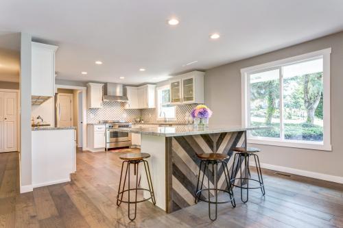 Veľká kuchyňa s bielym nábytkom a barovým sedením