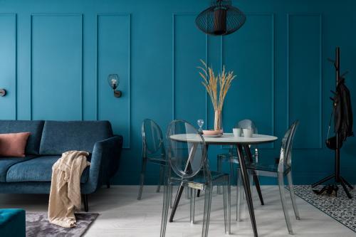 Okrúhly stôl a priehľadné stoličky v modrej obývačke