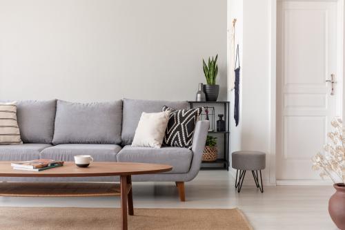 Sivá pohovka a drevený stolík v škandinávskom štýle