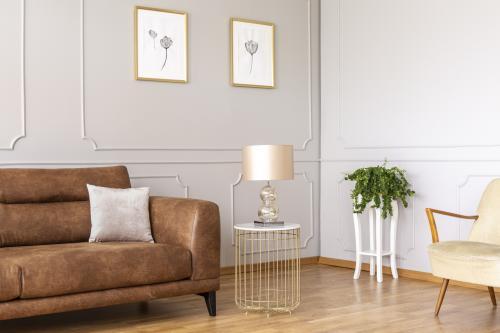Kožená pohovka a zlatý odkladací stolík s lampou