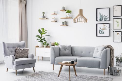 Sivá pohovka a kreslo ušiak v škandinávskej obývačke