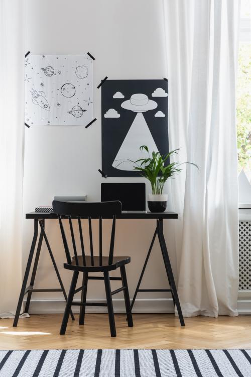 Malý písací stôl a stolička v čiernobielej študentskej izbe