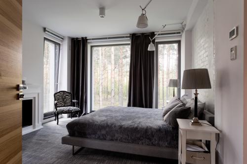 Pohodlná posteľ a čierne závesy vo veľkej spálni
