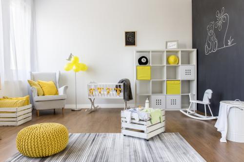 Biele kreslo ušiak a žltý puf v priestrannej detskej izbe