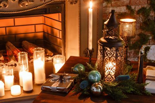 Biele sviečky a kovový lampáš s vianočnými dekoráciami