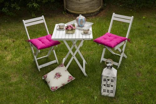 Biely záhradný stôl a stoličky s ružovými doplnkami