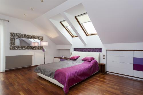Manželská posteľ so záhlavím, biele komody s fialovými tónmi, ozdobné zrkadlo