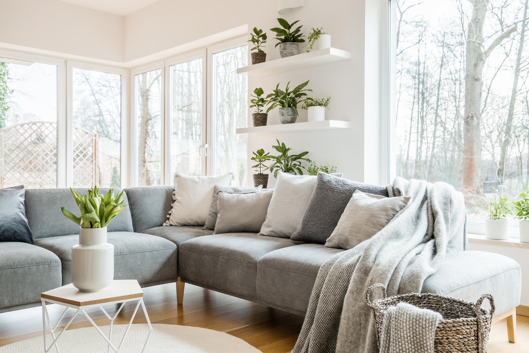 Sivá pohovka vo svetlej obývačke rodinného domu