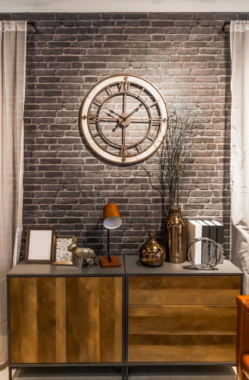 Veľké nástenné hodiny a elegantná komoda v industriálnom štýle