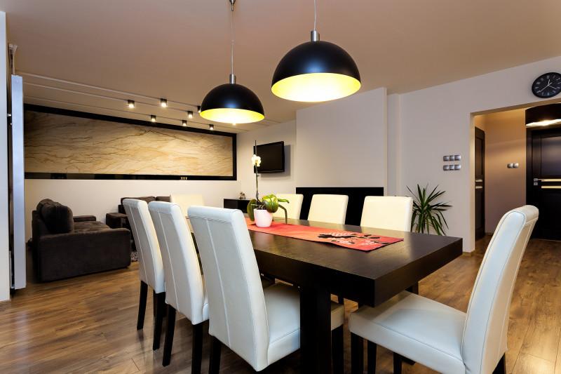 Tmavý jedálenský stôl s bielymi čalúnenými stoličkami