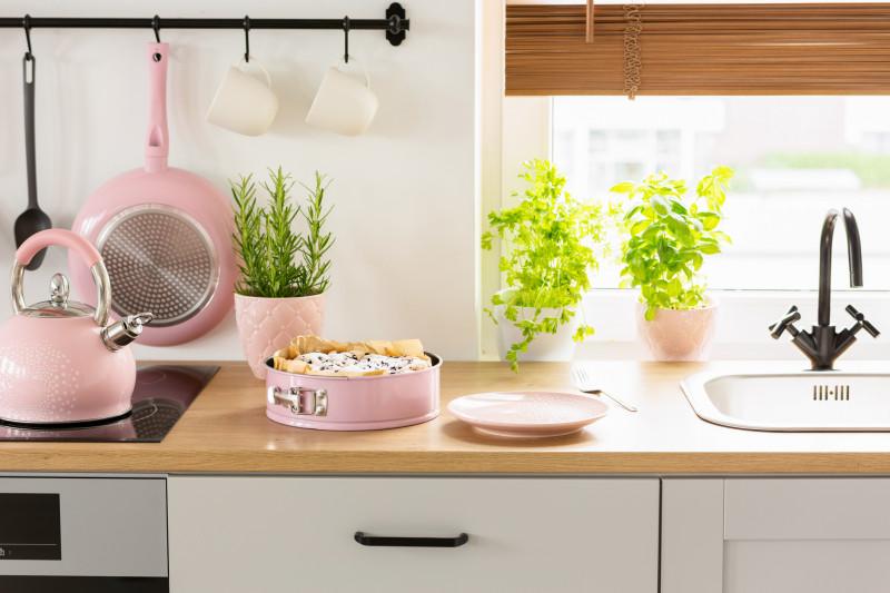 Biela kuchynská linka s ružovými doplnkami v retro štýle