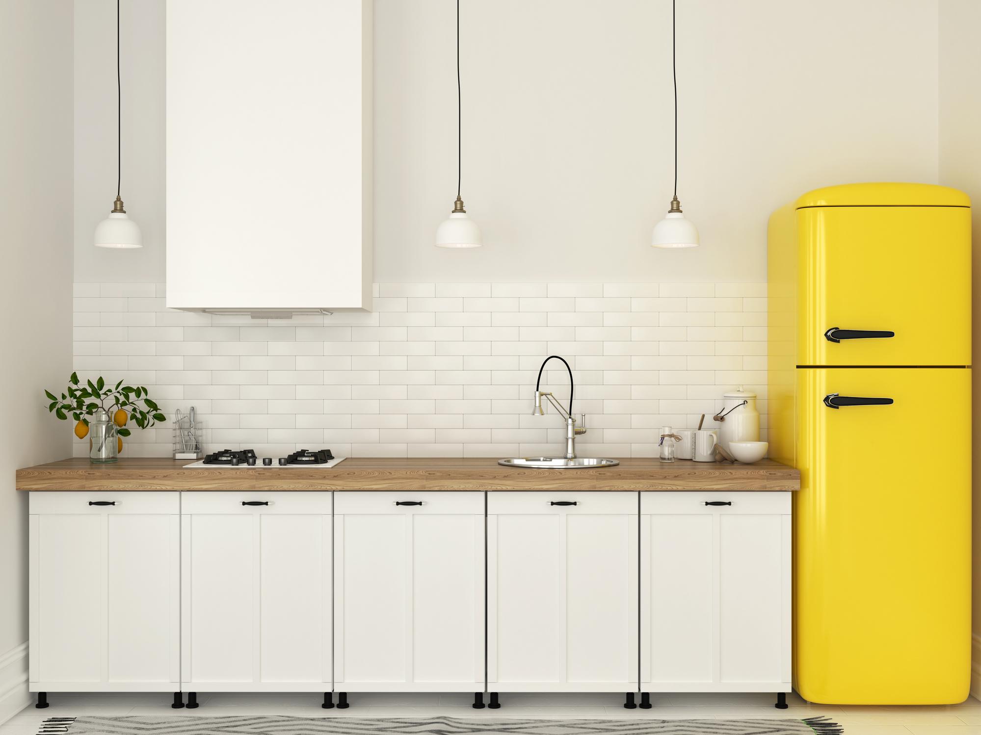 Žltá retro chladnička v malej bielej kuchyni